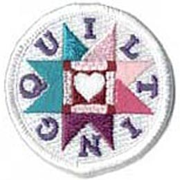 This round, white, merrow bordered patch has a white heart inside a square frame and surrounded by a starburst pattern. The word \'\'Quilting\'\' is formed with each individual letter placed inside the recess of the starburst pattern.