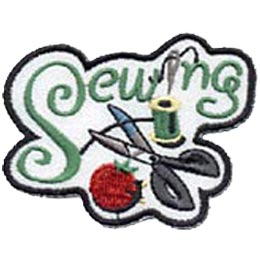 The word \'\'Sewing,\'\' where the \'I\' is replaced by a needle, is embroidered at the top of this patch. A spool of thread, scissors, and a pin cushion rests at the bottom.