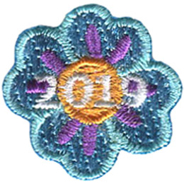 A blue flower with four petals and a yellow center. The date \'2019\' rests in the middle of this one inch flower.