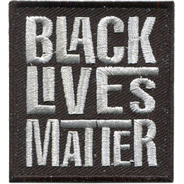 A black rectangle has the words Black Lives Matter embroidered in grey thread. Each word is stacked on top of the next.