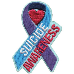 The purple and blue suicide awareness ribbon is displayed with a red heart inside the curl of the ribbon. The fore of the ribbon is blue and has the word \'Suicide\' on it. \'Awareness\' sits just underneath at the same angle.