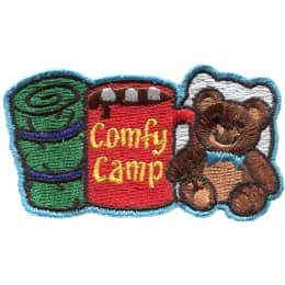 From left to right is a sleeping bag, a mug of coco with the words 'Comfy Camping' on the side, and a teddy bear with a pillow behind it.