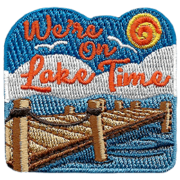 This crest is the picture of relaxation. Gulls fly in a blue, sunny sky above white puffy clouds. A wooden dock extends into a calm lake. The text, \'We\'re On Lake Time,\' sits in the sky.