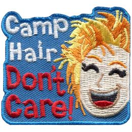 The words \'Camp Hair Don\'t Care\' stack on top of one another and are embroidered next to a smiling girl with really messy blonde hair.
