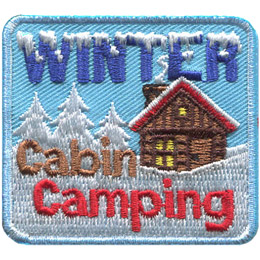 A cozy log cabin sits in a winter wonderland, surrounded by frost covered trees and a blanket of snow. The words \'Winter Cabin Camping\' are embroidered in blue, brown, and red threads (in that order).