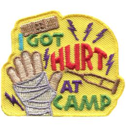 Purple lightning bolts of pain shoot off a bandaged hand. The words 'I Got Hurt At Camp' sit to the right of the image. A syringe rests between the words 'Hurt' and 'At Camp.'