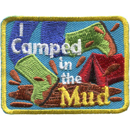 A person wearing bright green boots splashes in a mud puddle. The words 'I Camped in the Mud' are accented by a red tent in the background.