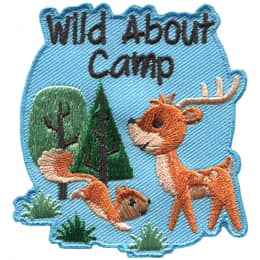 A deer and a squirrel face each other with two trees in the background. Text at the top of the crest read \'Wild About Camp\'.