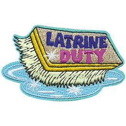 This bristled scrub brush has the words Latrine Duty on the wooden backing. There is a puddle underneath the scrubber.