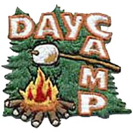 Evergreen trees form the backdrop of this roughly square patch. The words ''Day Camp'' form an upside down L shape running along the top of the patch and down the right hand side. A marshmallow on a stick is browning over a blazing campfire.