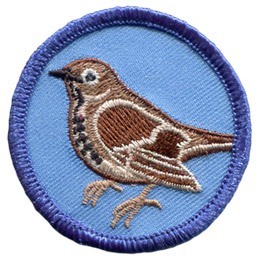 A beautiful brown thrush is displayed in this round, merrow bordered patch.