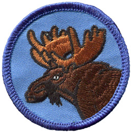 A brown furred moose with large scoop antlers looks over his shoulder while he is munching on a bit of grass. This circle badge has a merrow border.