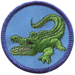 This round badge displays a green alligator with a its mouth open and it's sharp teeth on display. The 'gator's n tail on the right and head on the left.