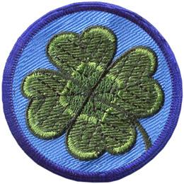 This circular patch displays a four-leaf shamrock on a background of blue.