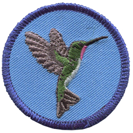 A hummingbird with wings spread wide open faces the right edge of this round circle badge.