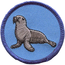 This round circle badge has a blue background with a sea lion in the foreground. The sea lion has its front propped up by its two flippers.