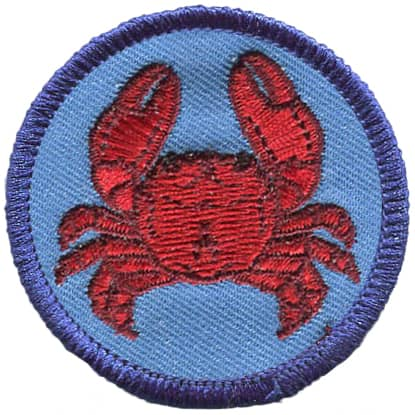 A crab is viewed from the top down on this circular crest.