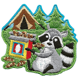 A raccoon happily munches on a box of chocolate chip cookies that it swiped from a tent.