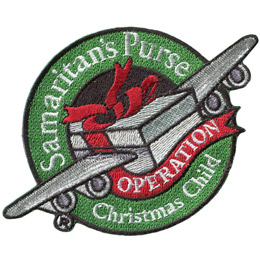 From the center outwards, this patch displays a shoe box tied closed with a red ribbon and with two airplane wings. The gift box is coming out of a green ring with the text \'Samaritan\'s Purse\' at the top of the hoop and \'Christmas Child\' embroidered at the bottom. A red, ribbon comes off the shoebox and forms a banner under the plane. This banner reads \'Operation\' on it. This is Samaritan\'s Purse\'s Operation Christmas Child patch.
