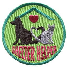 A dog and cat sit opposite each other and curl their tails, forming a heart together. Both creatures sit under a roof with a heart on it. The text \'Shelter Helper\' is embroidered underneath the animals.