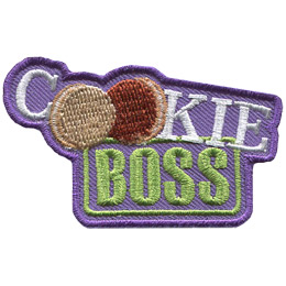 This crest is comprised of the words 'Cookie Boss.' 'Cookie' is written on a diagonal slant and the word's double 'o' has been replaced by vanilla and chocolate cookies. The word 'Boss' is underneath and looks like it has been stamped.