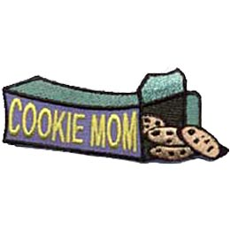 A box of cookies lies on its side as it spills out chocolate chip cookies. The words ''Cookie Mom'' are embroidered on the side of the box.