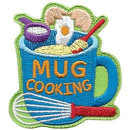Flour, egg, and butter are being placed in a mug that has the words \'Mug Cooking\' on the side.