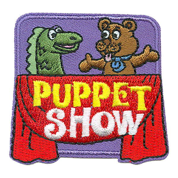 A dragon and a bear puppet are acting out a scene. A red throw is draped over the stage with the words \'Puppet Show\'.