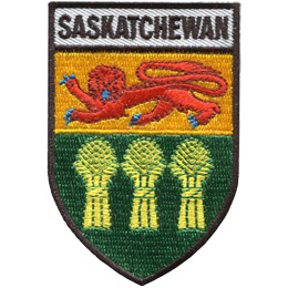 This shield shaped badge is broken into three horizontal sections. The top most bar has the name 'Saskatchewan'. The second section has a yellow background with a red lion filling the space. The last section displays a three wheat stacks standing on a green background.