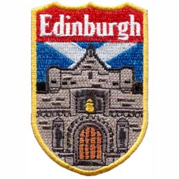 An embroidered image of a castle dominates this shield shaped patch. The word ''Edinburgh'' sits at the top of the emblem. The blue and white crossed Scottish flag is pictured in the background.
