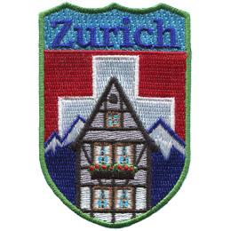 This shield patch depicts a Swiss Chalet in front of the Alpine mountain range which, itself, is situated before the white cross and red background flag of Switzerland. The top of the shield has 'Zurich' embroidered in blue threads.