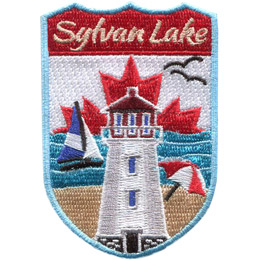 This crest displays a lighthouse front and center. Behind the lighthouse (bottom of the patch up) is a sandy beach, the waves of a lake, a maple leaf on a white background, and the words 'Sylvan Lake'. An umbrella is open on the beach, a sail boat rides the waves, and two birds fly in the white background.