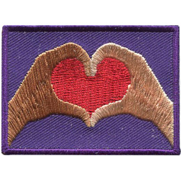 Two hands form a red heart on a purple background. The left hand is a brown colour and the right is a beige.