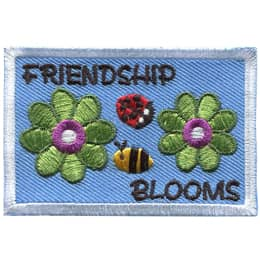 Two green petaled flowers bloom on either end of this rectangular patch. A ladybug and bumblebee sit in the middle. At the top is the text \'Friendship\' and at the bottom is \'Blooms\'.