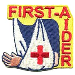 A person's shoulders and arm are visible in this yellowed background patch. The person's arm is in a white sling with a red cross displayed on the front. The word ''First-Aider'' is displayed in a backwards and upside down L shape running along the top and down the right hand side of the crest.