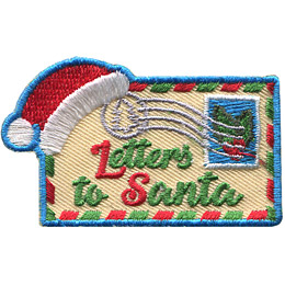 A tan envelope with a red and green patterned border has the words 'Letter to Santa' embroidered on the center. A postage stamp displaying holy sits in the top right corner and a Santa hat rests on the envelope in the top left corner.