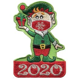 A male Christmas elf stands on a red box with 2020 embroidered in metallic threads on it. He wears a red mask with a silver metallic snowflake on its front, a red and green hat, and green pointed shoes.