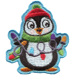 A happy penguin is wearing a toque (or beanie), a scarf, and holding a string of Christmas lights in his flippers.