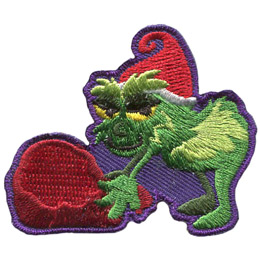 A fuzzy green humanoid, wearing a Santa hat, is bending over to pick up a red sack stuffed full. This Grinchy character has a satisfied smirk on his face.