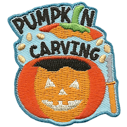 Seeds fly as the top is removed from a pumpkin that has been carved as a Jack-O-Lantern. The words \'Pumpkin Carving\' surround the removed top.