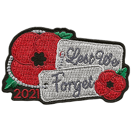 This Remembrance Day memento displays two poppies with military dog tags that say, \'Lest We Forget\'.
