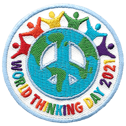 This round crest has a peace sign in the middle decorated with the ocean and contents of the world. Outside the peace sign is a white ring with outlines of the top half of people joined hand in hand. The other half of the ring has the text \'World Thinking Day 2021\'.