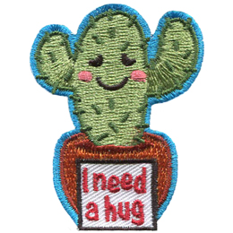 A two-armed cactus has a embarrassed smile as the sign in front of its pot reads I need a hug.