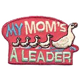 A mother duck leads four little ducklings through a pond. The words ''My Mom's'' rests above the row of ducks and ''A Leader'' sits below.