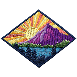 This diamond shaped badge depicts a sun rising behind a mountain. The sun casts its rays over a lake surrounded by a forest.
