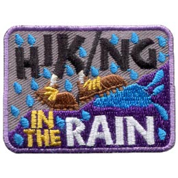 A set of shoes splashes in a puddle as they walk through a rain storm. The word ''Hiking'' is embroidered at the top of the patch and ''In The Rain'' at the bottom.