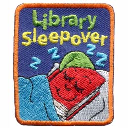 A red book wears a green night cap as it sleeps soundly in a comfy bed with a blue blanket pulled up snugly. The words ''Library Sleepover'' are embroidered along with four ''Z's'' above the book's head.