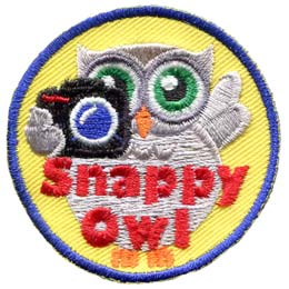 A grey owl holds a camera with his left wing while the other is up in the air. The words ''Snappy Owl'' are written in red near the bottom of the crest.