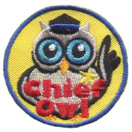 An owl has one wing on his hip and the other raised in a ''stop'' motion. He wears a chief's hat and a star badge on his chest. The words, ''Chief Owl'' are embroidered in red.
