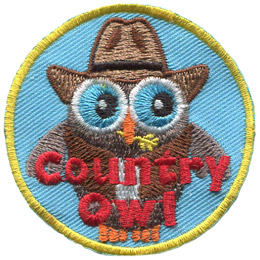 A 'Country Owl' is decorated with a cowboy hat, vest, and white undershirt. The owl holds a stalk of wheat in it's beak.